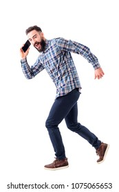 Young adult bearded business man running and talking on the cell phone. Full body length portrait isolated on white background.