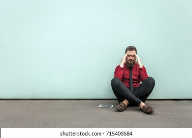 Young adult bearded businessman sits on the ground. have headache and migraine. Outdoor, gray wall.