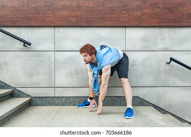 Young adult bearded and redhead man looking forward and doing stretching. Outdoor