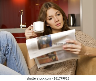 young adult beautiful brunette woman drinking coffee and reading newspaper in luxury apartment