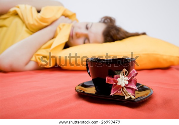 Young adult beautiful girl with a cup of coffee (focus on cup)