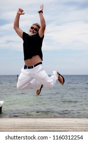 A young adult in a black shirt, white trousers and sandals jumps over a wooden pier on the Mediterranean coast.