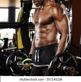 Young adult bodybuilder doing weight lifting in gym.