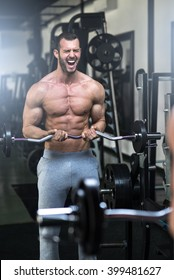 Young adult bodybuilder doing weight lifting in gym while screaming