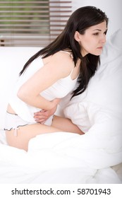 young adult brunette woman feeling pain in bed