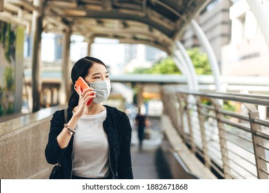 Young adult business asian working woman wear face mask for protect virus corona or covid19 and air pollution. Using mobile phone for talk. Urban people lifestyle with public health on day concept.