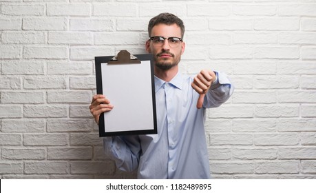Young adult business man over brick wall holding clipboard with angry face, negative sign showing dislike with thumbs down, rejection concept