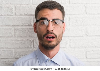 Young adult business man standing over white brick wall scared in shock with a surprise face, afraid and excited with fear expression