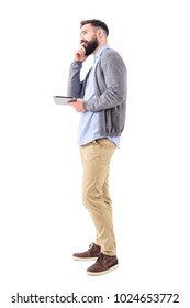 Young adult business man with tablet thinking and looking up. Full body length portrait isolated on white studio background.