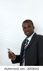 young adult businessman holding mobile phone. Shadows from venetian blinds on wall. Copy space