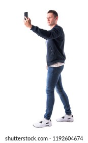 Young adult casual man taking picture with mobile phone. Side view. Full body isolated on white background.