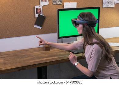 Young adult Caucasian female using holographic augmented reality glasses, creating a model on a computer screen. Green screen chroma key