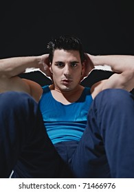 young adult caucasian male in blue sportswear exercising abdominals on black background, looking at camera. Vertical shape, front view, copy space