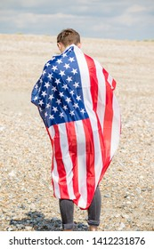 Young adult caucasian male holding on a beach holding the flag of The United States
