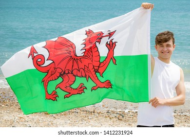 Young adult caucasian male holding on a beach holding the flag of Wales