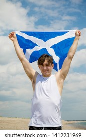 Young adult caucasian male holding on a beach holding the flag of Scotland