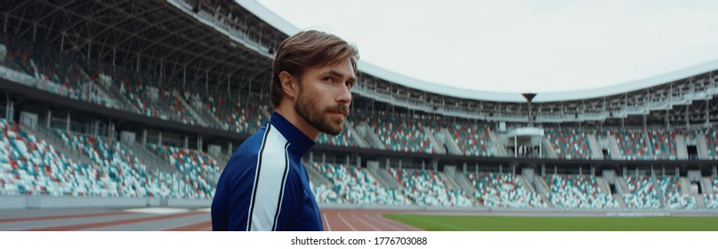 Young adult Caucasian male sportsman soccer player standing and admiring a large empty stadium