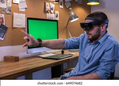 Young adult Caucasian male using holographic augmented reality glasses, creating a model on a computer screen