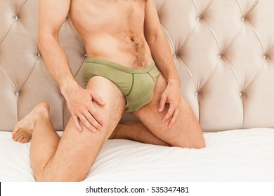 Young adult Caucasian man in green underpants on the bed, male beauty and sexual health theme, studio photo