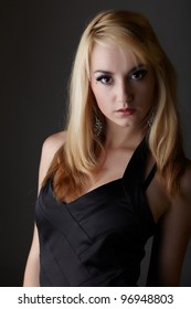 Young adult caucasian woman with blonde hair and prominent jewelry on a neutral grey background with a little black dress and big brown eyes