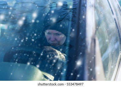 Young adult caucasian woman can not start car on cold snowy winter day