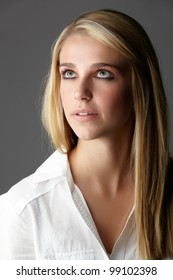 Young adult caucasian woman with long blonde hair and green eyes wearing a plain white shirt with flawless skin and natural makeup.