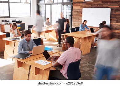 Young adult colleagues working in a busy office, motion blur
