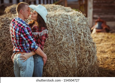 young adult couple embracing near hay