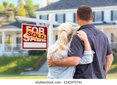 Young Adult Couple Facing Front of Sold Real Estate Sign and House.