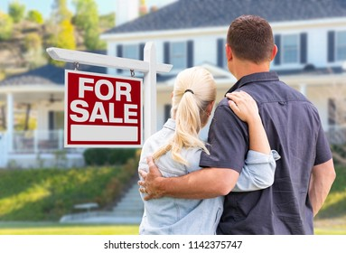 Young Adult Couple Facing Front of For Sale Real Estate Sign and House.