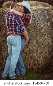young adult couple kissing near hay