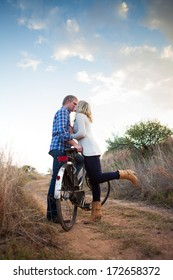 Young adult couple with old bicycle kissing in dirt road