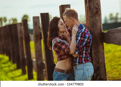 young adult couple on the farm standing near fence, man in the foreground