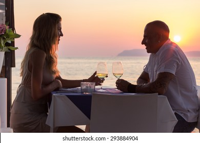 Young adult couple on vacation drinking wine in restaurant