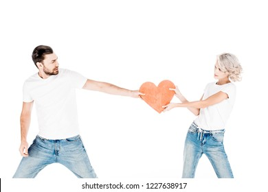 Young adult couple pulling one red big heart shape to each other isolated on white