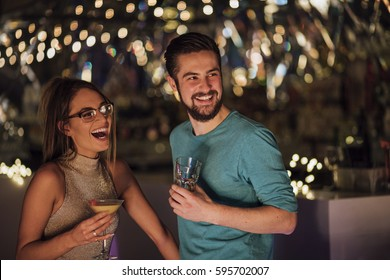 Young adult couple are socialising in a nightclub with cocktails. They are laughing and looking at someone out of the frame.
