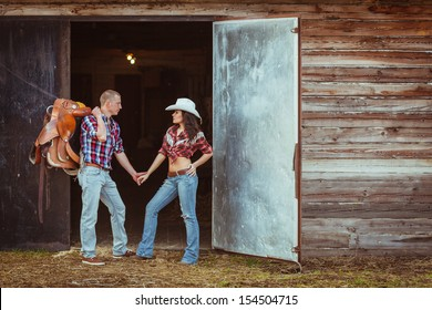young adult couple standing near stable