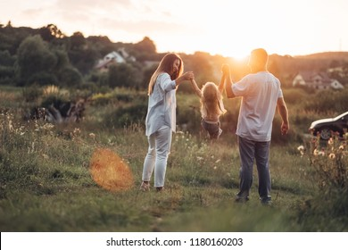 Young Adult Couple with Their Little Daughter Having Fun in the Park Outside the City, Family Weekend Picnic Concept, Three People Enjoying Summer