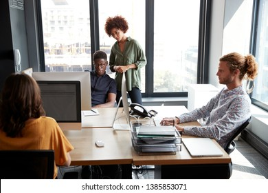 Young adult creatives working together at a desk in a casual office, close up
