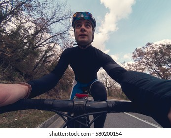 Young adult cyclist man takes a selfie during a training on his bicycle. Vintage toned. Point of view.