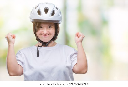 Young adult cyclist woman with down syndrome wearing safety helmet over isolated background celebrating surprised and amazed for success with arms raised and open eyes. Winner concept.