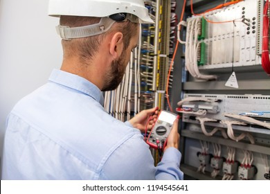 Young adult electrician builder engineer inspecting electric equipment in distribution fuse box. Electrical engineer worker in control panel. Maintenance electro box with multimeter.