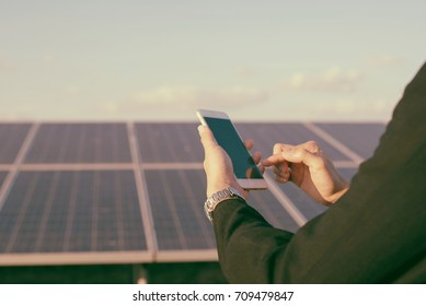 Young adult electrician builder engineer or worker  testing electronics or inspecting  electrical installation system in a Solar Photovoltaic Plant with smartphone