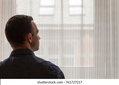 Young adult European man stands near urban window and looks outside, studio photo with selective focus