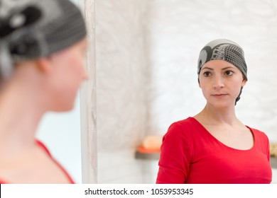 Young adult female cancer patient wearing headscarf looking in the mirror. Tired, exhausted, depressed and scared cancer patient.