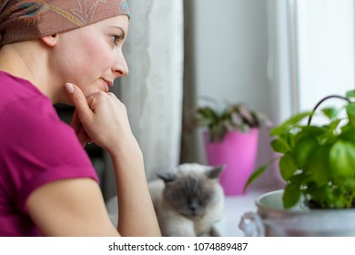 Young adult female cancer patient wearing headscarf and bathrobe sitting in the kitchen with her pet cat, looking out window.