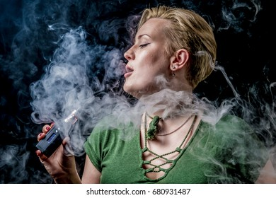 Young adult female exhaling smoke clouds from electronic cigarette