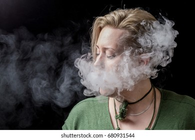 Young adult female exhaling smoke from electronic cigarette