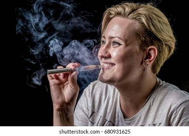 Young adult female exhaling smoke clouds from electronic cigarette and smiling