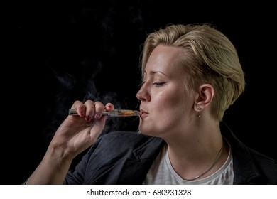 Young adult female inhaling smoke from electronic cigarette